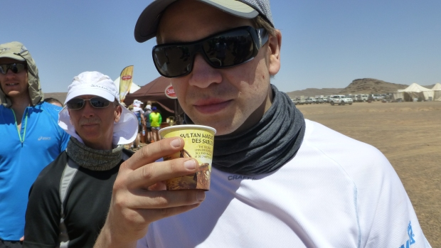 Jakob sampling Sultan's sponsor tea, a sugary sweet tea we were served every time we passed the finish line