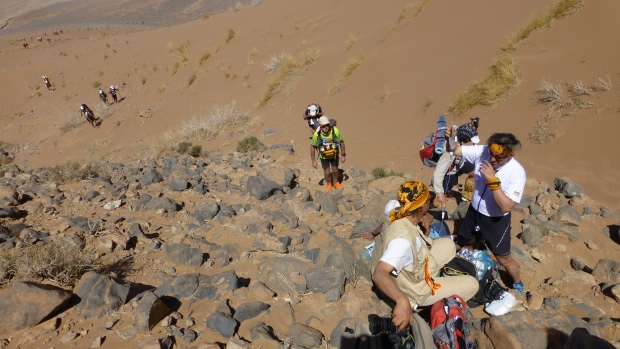 A runner getting medical attention on the steep incline to the top of Jebel Otfal.